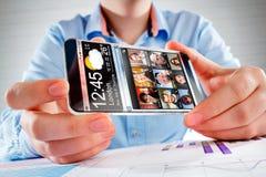有透明屏幕的智能手机在人的手上。 免版税库存照片