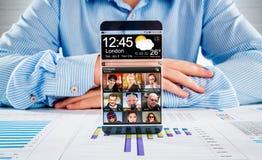 有透明屏幕的智能手机在人的手上。 图库摄影