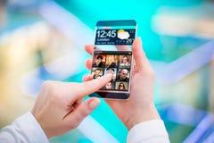 有透明屏幕的智能手机在人的手上。 库存照片