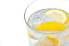 有透明的水、柠檬和冰块的一个玻璃烧杯 免版税库存图片