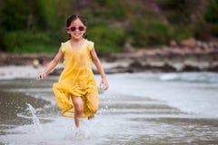 有逗人喜爱的亚裔小孩的女孩在海滩的使用的乐趣和奔跑 免版税库存照片