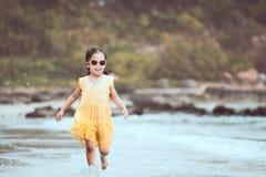 有逗人喜爱的亚裔小孩的女孩在海滩的使用的乐趣和奔跑 免版税图库摄影