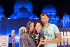 有逗人喜爱的作梦在扎耶德Mosque回教族长阿布扎比佩带的abaya的, paranja盛大清真寺的儿子和父亲的母亲在夜t 免版税库存图片