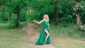 有逗人喜爱的凸起的腹部的一个可爱的怀孕的女孩,她拥抱,在一个明亮的夏天森林里站立,投掷 股票录像