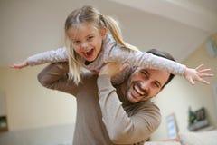 有逗人喜爱的女儿的年轻爸爸在家 库存照片