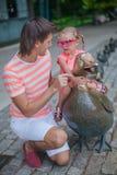 有逗人喜爱的女儿的年轻愉快的父亲在公园 免版税图库摄影