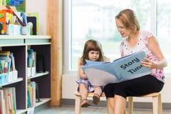 有逗人喜爱的女孩阅读书的老师在图书馆里 免版税库存照片