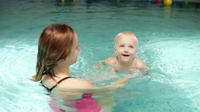 有逗人喜爱的婴孩与他的母亲的游泳教训 教他们的婴孩的健康家庭游泳在游泳池 年轻 股票视频