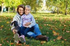 有逗人喜爱的小女孩的微笑的妇女在秋天停放 图库摄影