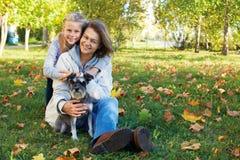 有逗人喜爱的小女孩的微笑的妇女在秋天停放 免版税库存照片
