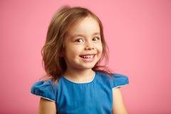 有逗人喜爱的微笑和恳切的神色的美丽的惊奇的儿童女孩,是在一种好心情,表示喜悦和高兴,关闭 免版税库存照片