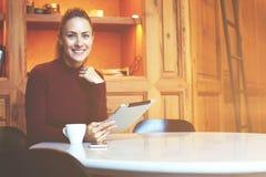 有逗人喜爱的微笑的女性使用数字式片剂,当放松在休闲时间时 免版税库存照片