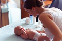 有逗人喜爱的微笑的妈妈照顾她在婴孩改变的桌上的新出生的男孩 免版税库存图片