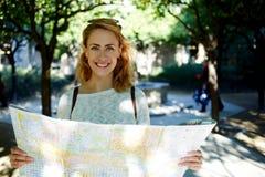 有逗人喜爱的微笑的愉快的女性学习地图集的在走前在外国城市在夏天旅行期间 免版税库存图片
