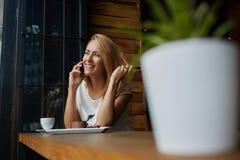 有逗人喜爱的微笑的愉快的美丽的女性有手机交谈,当坐在咖啡店在休闲时间时 库存照片