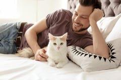有逗人喜爱的猫的年轻人在床上 免版税库存图片