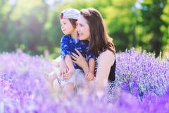有逗人喜爱的男孩的愉快的妇女淡紫色背景的 免版税库存照片