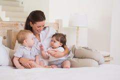 有逗人喜爱的男婴和女孩的愉快的母亲 库存图片
