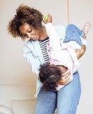 有逗人喜爱的矮小的女儿的可爱的甜年轻美国黑人的母亲,在家垂悬,获得演奏微笑的乐趣 免版税库存照片