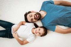 有逗人喜爱的矮小的女儿的成人愉快的有胡子的人在床上说谎在床垫商店 库存图片