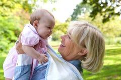 有逗人喜爱的婴孩的愉快的祖母 免版税图库摄影