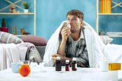 有通气管的有胡子的病的人在家坐沙发 病症,流行性感冒,痛苦概念 家庭放松 医疗保健 免版税库存照片