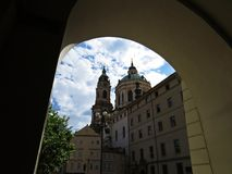 有通过段落拱道被看见的多云天空的老历史的教会 免版税图库摄影