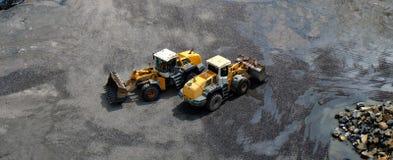 有通过的前面桶的两辆轮子装载者车,横渡在相反方向在co的地球运动的工作期间 免版税图库摄影