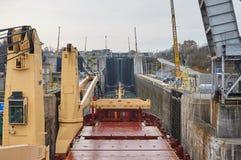 有通过锁的两台起重机的货船船在大湖,冬时的加拿大 免版税库存图片