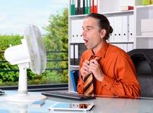 有通风设备的商人在他的书桌在summerly热的办公室 免版税库存照片