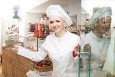 有遇见顾客的帽子的厨师在面包点心店的门 免版税库存照片