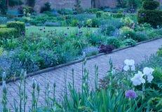 有道路的运行在花床之间的-图象美丽的英国村庄国家庭院 免版税库存照片