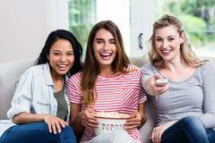 有遥控和玉米花的快乐的女性朋友在家 免版税库存照片