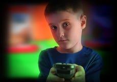 有遥控的儿童观看的电视 免版税库存图片