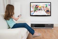 有遥控的女孩在电视前面 免版税库存图片