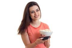 有遥控的好美丽的女孩在她的手和板材玉米花特写镜头上 图库摄影