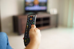 有遥控的妇女坐的观看的电视改变的渠道 库存图片