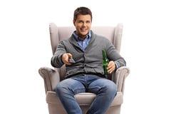 有遥控的年轻人和在扶手椅子的一啤酒瓶 免版税库存图片