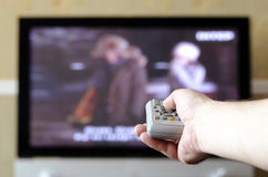 有遥控的电视的手 免版税库存图片