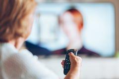 有遥控观看的电视的资深妇女 库存图片