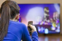 有遥控观看的聪明的电视的少年女孩 图库摄影