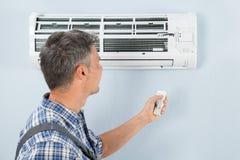 有遥远的控制器的安装工运行的空调器 库存图片