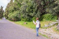 有避过古老废墟的地图的游人在罗马老镇,阿皮亚Antica方式,早意大利历史,旅行destin遗产  免版税库存图片