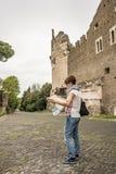 有避过古老废墟的地图的游人在罗马老镇,阿皮亚Antica方式,早意大利历史,旅行destin遗产  图库摄影