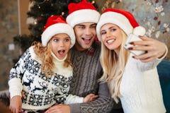有那些的滑稽的年轻父母圣诞老人` s帽子的ta小女儿 免版税库存照片