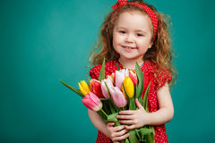 有郁金香大花束的美丽的小女孩  免版税库存图片