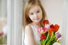 有郁金香的可爱的小女孩由窗口 免版税库存图片