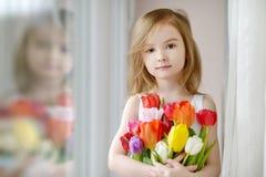 有郁金香的可爱的小女孩由窗口 免版税图库摄影