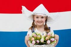 有郁金香花和荷兰旗子的荷兰孩子 免版税库存图片