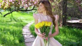 有郁金香花束的美丽的妇女在开花的庭院的 股票录像